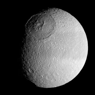 "<h1>PIA08400:  The Crown of Tethys</h1><div class=""PIA08400"" lang=""en"" style=""width:800px;text-align:left;margin:auto;background-color:#000;padding:10px;max-height:150px;overflow:auto;""><p>The vast expanse of the crater Odysseus spreads out below Cassini in this mosaic view of Saturn's moon Tethys.</p><p>The crater (450 kilometers or 280 miles across) is a remarkably well-preserved example of an ancient multi-ringed impact basin: The outer ring is defined by steep, cliff-like walls that descend to generally broad internal terraces. The inner ring is formed by a prominent, crown-shaped, 140-kilometer (88-mile) diameter circular band of icy mountains. Multi-ring basins are seen on rocky bodies as well as icy ones.</p><p>The complex internal structure and multi-ringed nature of these very large basins are believed to arise from the rebound of intense shock waves that penetrated the body at the time of impact.</p><p>Tethys is 1,071 kilometers (665 miles) across.</p><p>This mosaic was assembled from four clear filter, narrow-angle camera images. The view is an orthographic projection centered on 3 degrees south latitude, 119 degrees west longitude and has a resolution of 572 meters (0.35 mile) per pixel. An orthographic view is most like the view seen by a distant observer looking through a telescope. North is up.</p><p>The view was obtained by the Cassini spacecraft on Aug. 30, 2007, from a distance of approximately 97,000 kilometers (60,000 miles) and at a sun-Tethys-spacecraft, or phase, angle of 51 degrees.</p><p>The Cassini-Huygens mission is a cooperative project of NASA, the European Space Agency and the Italian Space Agency. The Jet Propulsion Laboratory, a division of the California Institute of Technology in Pasadena, manages the mission for NASA's Science Mission Directorate, Washington, D.C. The Cassini orbiter and its two onboard cameras were designed, developed and assembled at JPL. The imaging operations center is based at the Space Science Institute in Boulder, Colo.</p><p>For more information about the Cassini-Huygens mission visit <a href=""http://saturn.jpl.nasa.gov"">http://saturn.jpl.nasa.gov/home/index.cfm</a>. The Cassini imaging team homepage is at <a href=""http://ciclops.org"">http://ciclops.org</a>.</p><br /><br /><a href=""http://photojournal.jpl.nasa.gov/catalog/PIA08400"" onclick=""window.open(this.href); return false;"" title=""Voir l'image 	 PIA08400:  The Crown of Tethys	  sur le site de la NASA"">Voir l'image 	 PIA08400:  The Crown of Tethys	  sur le site de la NASA.</a></div>"
