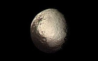 "<h1>PIA00348:  Iapetus Bright and Dark Terrains</h1><div class=""PIA00348"" lang=""en"" style=""width:325px;text-align:left;margin:auto;background-color:#000;padding:10px;max-height:150px;overflow:auto;"">Saturn's outermost large moon, Iapetus, has a bright, heavily cratered icy terrain and a dark terrain, as shown in this Voyager 2 image taken on August 22, 1981. Amazingly, the dark material covers precisely the side of Iapetus that leads in the direction of orbital motion around Saturn (except for the poles), whereas the bright material occurs on the trailing hemisphere and at the poles. The bright terrain is made of dirty ice, and the dark terrain is surfaced by carbonaceous molecules, according to measurements made with Earth-based telescopes. Iapetus' dark hemisphere has been likened to tar or asphalt and is so dark that no details within this terrain were visible to Voyager 2. The bright icy hemisphere, likened to dirty snow, shows many large impact craters. The closest approach by Voyager 2 to Iapetus was a relatively distant 600,000 miles, so that our best images, such as this, have a resolution of about 12 miles. The dark material is made of organic substances, probably including poisonous cyano compounds such as frozen hydrogen cyanide polymers. Though we know a little about the dark terrain's chemical nature, we do not understand its origin. Two theories have been developed, but neither is fully satisfactory--(1) the dark material may be organic dust knocked off the small neighboring satellite Phoebe and ""painted"" onto the leading side of Iapetus as the dust spirals toward Saturn and Iapetus hurtles through the tenuous dust cloud, or (2) the dark material may be made of icy-cold carbonaceous ""cryovolcanic"" lavas that were erupted from Iapetus' interior and then blackened by solar radiation, charged particles, and cosmic rays. A determination of the actual cause, as well as discovery of any other geologic features smaller than 12 miles across, awaits the Cassini Saturn orbiter to arrive in 2004.<br /><br /><a href=""http://photojournal.jpl.nasa.gov/catalog/PIA00348"" onclick=""window.open(this.href); return false;"" title=""Voir l'image 	 PIA00348:  Iapetus Bright and Dark Terrains	  sur le site de la NASA"">Voir l'image 	 PIA00348:  Iapetus Bright and Dark Terrains	  sur le site de la NASA.</a></div>"
