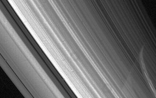 "<h1>PIA01962:  High-resolution view of Saturn's rings</h1><div class=""PIA01962"" lang=""en"" style=""width:750px;text-align:left;margin:auto;background-color:#000;padding:10px;max-height:150px;overflow:auto;"">Voyager 2 high-resolution view of Saturn's rings Aug. 23 at a range of 3.3 million kilometers (2 million miles). The planet's limb is visible through the C-ring and the inner part of the B-ring. The ring shadows have been obscured by the bright band of light, evident on Saturn's surface, that passed through the more transparent Cassini Division. The Cassini Division is the darker gap that extends from the lower center of this image to the upper left; it is about 5,000 km. (3,100 mi.) wide. Many bright and dark ringlets are seen throughout the complex ring system. The Voyager project is managed for NASA by the Jet Propulsion Laboratory, Pasadena, Calif.<br /><br /><a href=""http://photojournal.jpl.nasa.gov/catalog/PIA01962"" onclick=""window.open(this.href); return false;"" title=""Voir l'image 	 PIA01962:  High-resolution view of Saturn's rings	  sur le site de la NASA"">Voir l'image 	 PIA01962:  High-resolution view of Saturn's rings	  sur le site de la NASA.</a></div>"